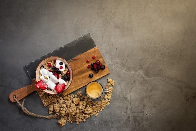 Bovenaanzicht van een gezond ontbijt met muesli, yoghurt en seizoensbessen op een concrete achtergrond