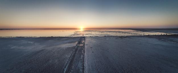 Bovenaanzicht van een glanzend zout roze meer en een pad erlangs