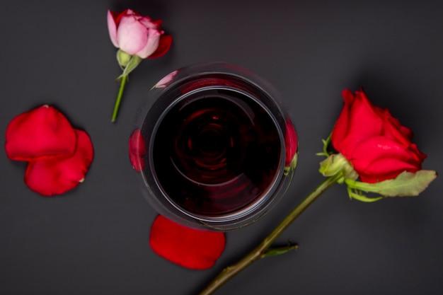 Bovenaanzicht van een glas wijn met rode kleur rozen op zwarte tafel
