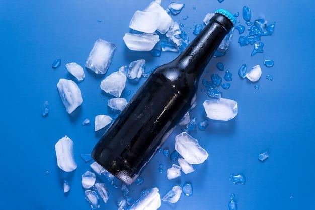 Bovenaanzicht van een glazen bierfles op een blauwe ondergrond met ijs