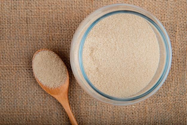 Bovenaanzicht van een glazen pot gevuld met gekorrelde bruine suiker op jute textuur achtergrond