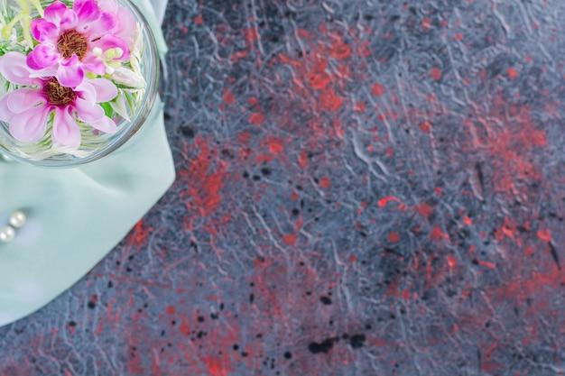 Bovenaanzicht van een glazen vaas met bloemen op tafelkleed.