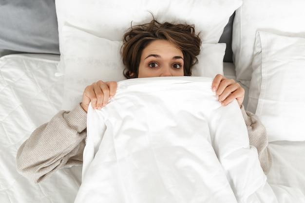 Bovenaanzicht van een glimlachend jong meisje dat 's ochtends in bed ontspant