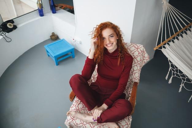 Bovenaanzicht van een glimlachende gelukkige vrouw zittend op een stoel