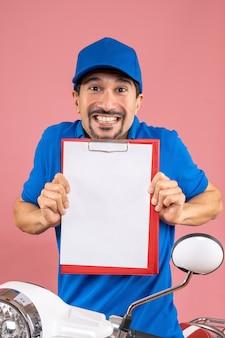 Bovenaanzicht van een glimlachende mannelijke bezorger met een hoed die op een scooter zit en document toont showing