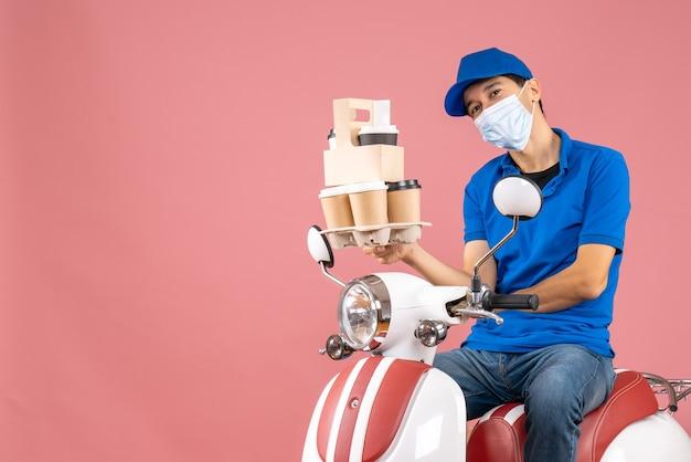 Bovenaanzicht van een glimlachende mannelijke bezorger met een masker die een hoed draagt die op een scooter zit en bestellingen aflevert op perzik