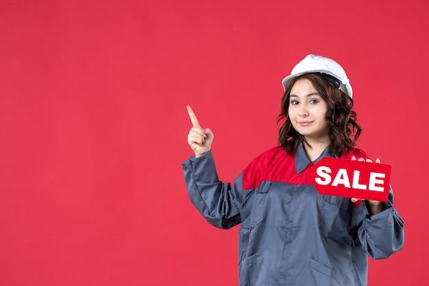 Bovenaanzicht van een glimlachende vrouwelijke bouwer in uniform met een helm en een verkooppictogram dat aan de rechterkant op geïsoleerde rode achtergrond omhoog wijst
