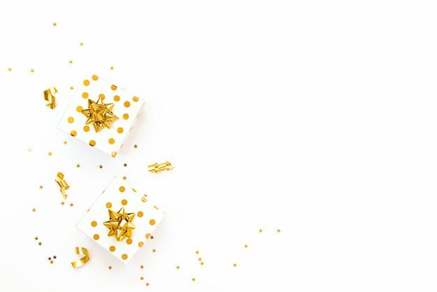 Bovenaanzicht van een gouden gestippelde geschenkdozen en stervormige gouden pailletten op een witte achtergrond. ruimte kopiëren.