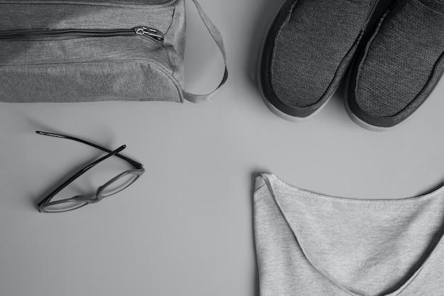 Bovenaanzicht van een grijs herenmode-t-shirt, bril, toilettas en een paar sneakers op grijs