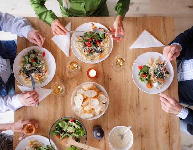 Bovenaanzicht van een groep senior vrienden op een etentje thuis, eten. een middenstuk.