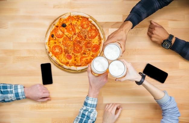 Bovenaanzicht van een groep vrienden die pizza eten en bier drinken