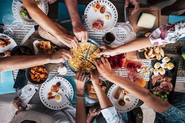 Bovenaanzicht van een groep vrienden die plezier hebben met samen eten tijdens de lunch