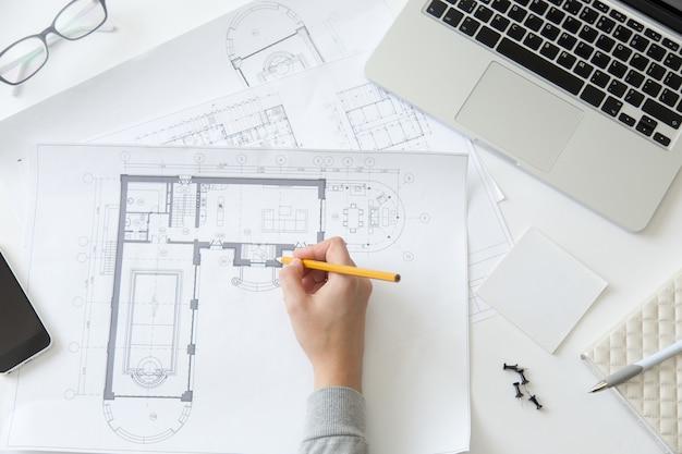 Bovenaanzicht van een hand die een architecttekening maakt