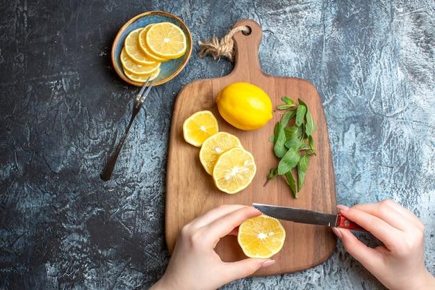 Bovenaanzicht van een hand die verse citroenen en munt hakt op een houten snijplank op donkere achtergrond