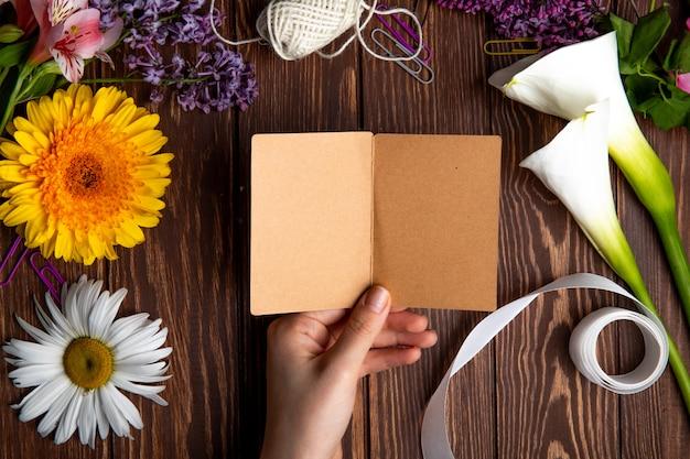 Bovenaanzicht van een hand met een briefkaart en gerbera met madeliefjebloemen op houten achtergrond