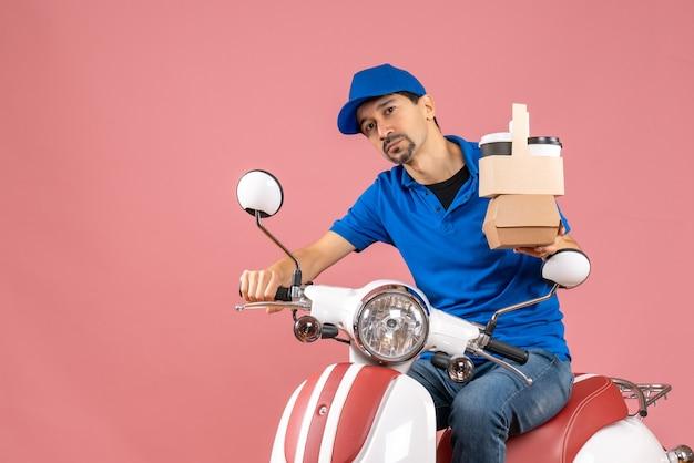 Bovenaanzicht van een hardwerkende koeriersman met een hoed die op een scooter zit en bestellingen op een pastelkleurige perzikachtergrond toont