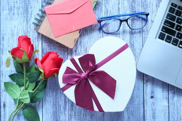 Bovenaanzicht van een hart vorm geschenkdoos en roze bloem op tafel