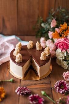 Bovenaanzicht van een heerlijke cake met kers op de top in de buurt van kleurrijke bloemdecoraties op een houten tafel
