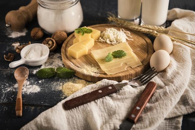 Bovenaanzicht van een heerlijke kaasschotel met melk, bloem en eieren op een tafel