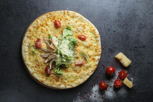 Bovenaanzicht van een heerlijke pizza met tomaten en kaas op een tafel