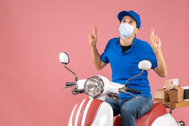 Bovenaanzicht van een hoopvolle bezorger met een medisch masker met een hoed die op een scooter zit en droomt over iets op een pastelkleurige perzikachtergrond