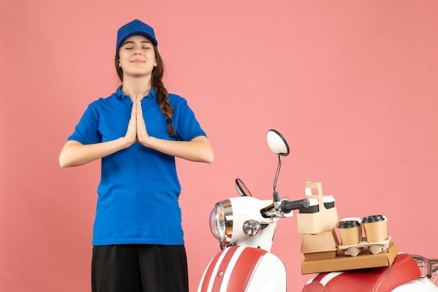 Bovenaanzicht van een hoopvolle koeriersdame die naast de motorfiets staat met koffie en kleine taarten erop en droomt van iets op een pastelkleurige perzikkleurige achtergrond