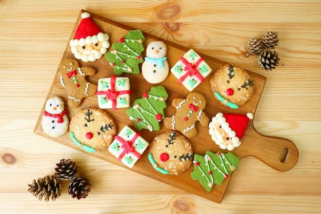 Bovenaanzicht van een houten dienblad vol smakelijke kerstkoekjes versierd met droge dennenappels