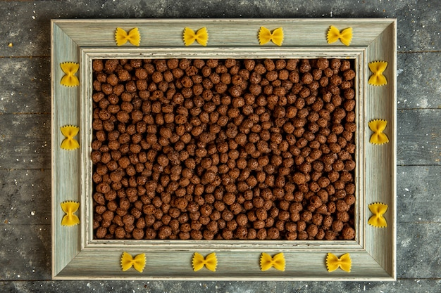 Bovenaanzicht van een houten fotolijst met farfalle pasta en gevuld met chocolade cornflakes corn balls