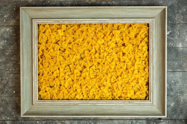 Bovenaanzicht van een houten frame gevuld met rauwe pasta farfalle