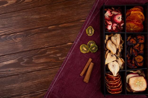 Bovenaanzicht van een houten kist met verschillende gedroogde vruchten op houten achtergrond met kopie ruimte