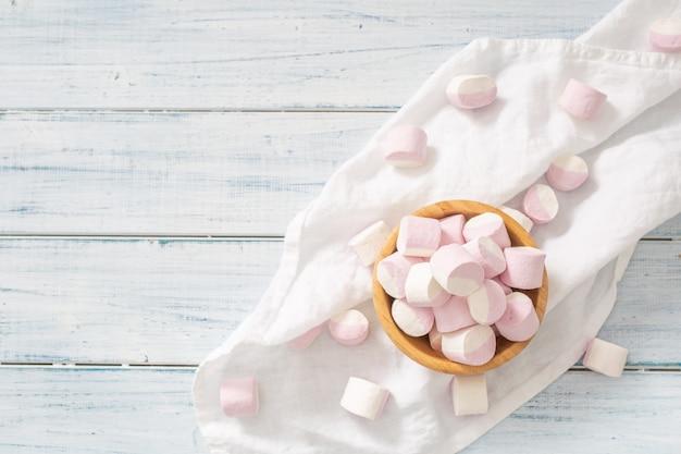 Bovenaanzicht van een houten kom vol roze en witte marshmallows met wat verspreid op een wit tafelkleed en een wit houten oppervlak.