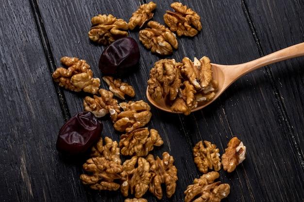 Bovenaanzicht van een houten lepel met walnoten en zoete gedroogde datum vruchten op rustieke