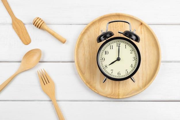 Bovenaanzicht van een houten schotel en eetgerei met een klok