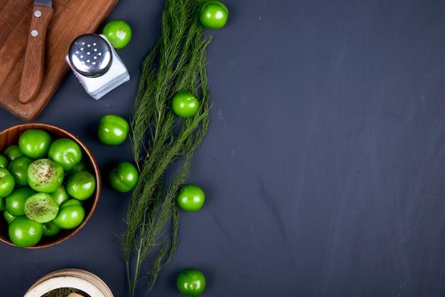 Bovenaanzicht van een houten snijplank met een mes, zoutvaatje, gedroogde pepermunt in een vijzel, venkel en zure groene pruimen in een houten kom op zwarte tafel met kopie ruimte