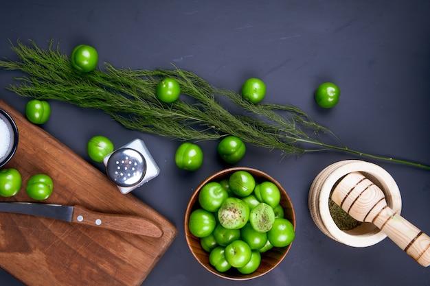 Bovenaanzicht van een houten snijplank met een mes, zoutvaatje, gedroogde pepermunt in een vijzel, venkel en zure groene pruimen in een houten kom op zwarte tafel