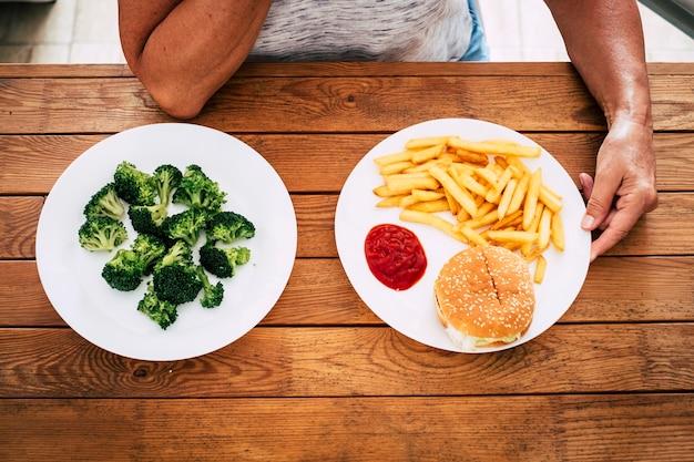 Bovenaanzicht van een houten tafel met twee borden met haburger en chips of groenten zoals broccoli - kiezen voor een gezonde of ongezonde levensstijl