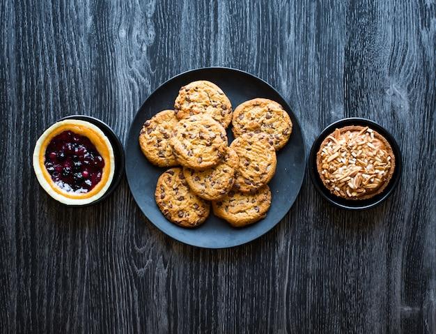 Bovenaanzicht van een houten tafel vol cakes, fruit, koffie, koekjes, kruiden en meer