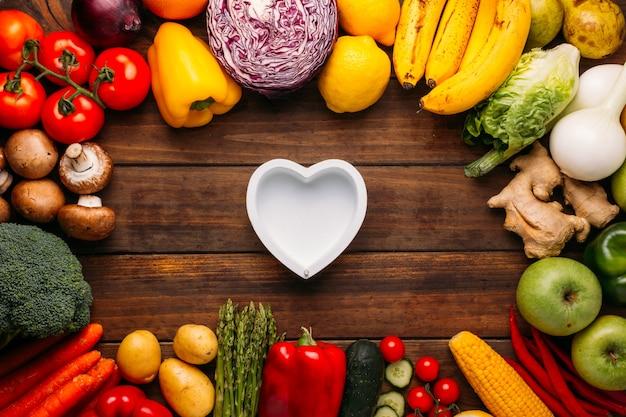 Bovenaanzicht van een houten tafel vol groenten en in het midden van de afbeelding een leeg hart