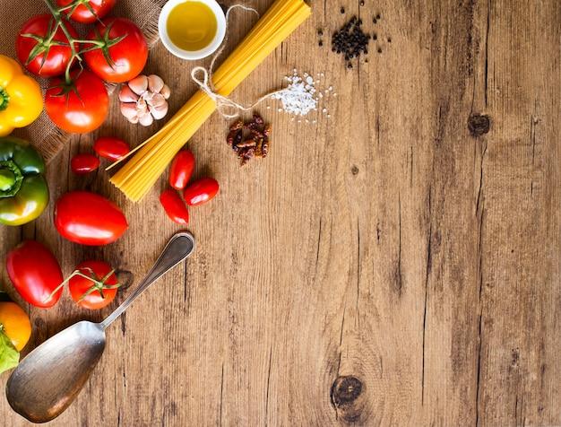 Bovenaanzicht van een houten tafel vol met italiaanse pasta ingradients zoals pepi tomaten olijfolie basi