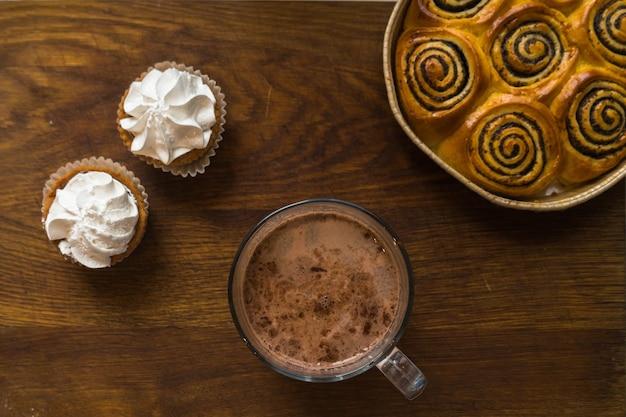 Bovenaanzicht van een houten tafel vol taarten en meer klassieke zoete etenswaren