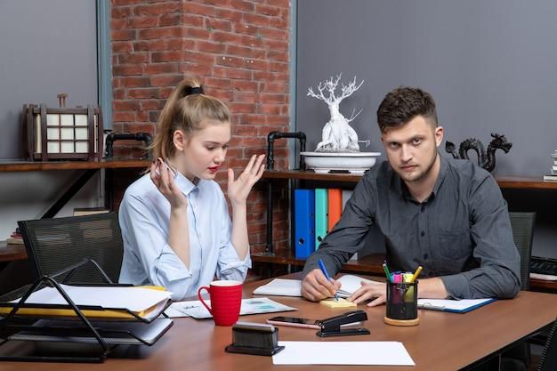 Bovenaanzicht van een jong gemotiveerd en hardwerkend kantoorteam gericht op één probleem in een kantooromgeving