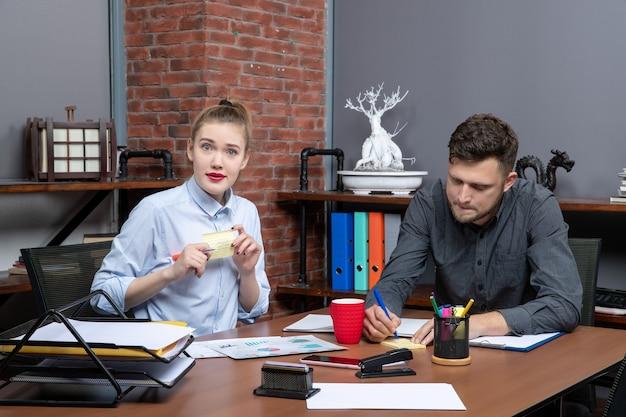 Bovenaanzicht van een jong gemotiveerd kantoorteam gericht op één probleem in een kantooromgeving