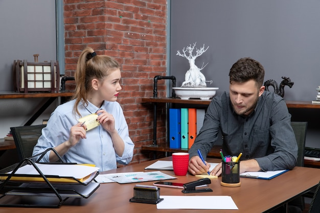 Bovenaanzicht van een jong grappig kantoorteam gericht op één probleem in een kantooromgeving
