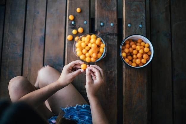 Bovenaanzicht van een jong meisje gele pruimen schoonmaken