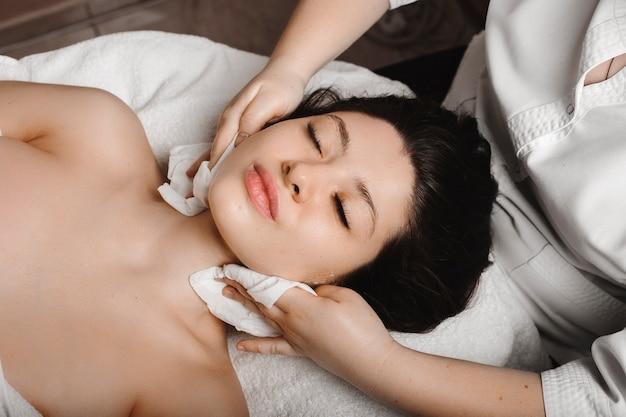 Bovenaanzicht van een jonge aantrekkelijke vrouw die anti-acneprocedures in wellness-kuuroord doet door een vrouwelijke schoonheidsspecialist.