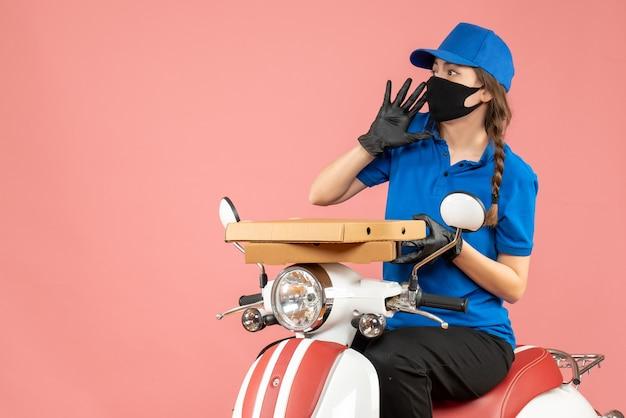 Bovenaanzicht van een jonge, bange vrouwelijke koerier met een medisch masker en handschoenen die op een scooter zitten en bestellingen afleveren op pastel perzik