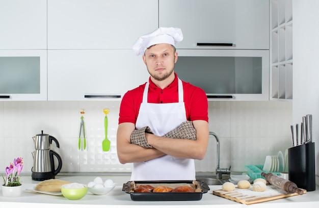 Bovenaanzicht van een jonge chef-kok die een houder draagt die achter de tafel staat met gebak-eierenrasp erop in de witte keuken
