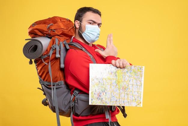 Bovenaanzicht van een jonge denkende reiziger die een medisch masker draagt met een rugzak met een kaart die op geel wijst