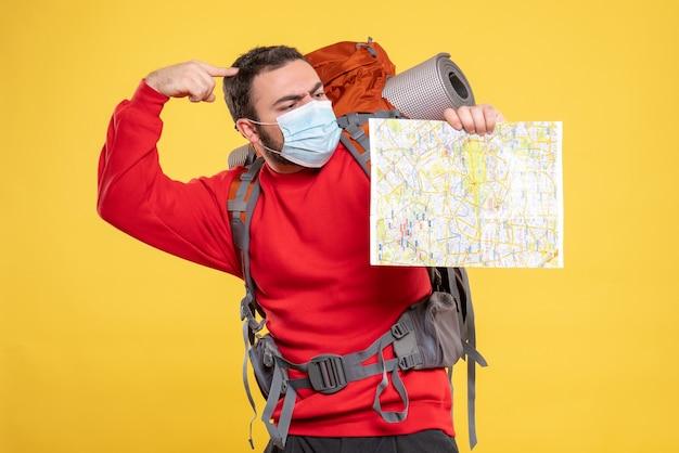 Bovenaanzicht van een jonge denkende reiziger die een medisch masker draagt met een rugzak met een kaart op geel