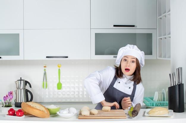 Bovenaanzicht van een jonge drukke vrouwelijke chef-kok in uniform die achter de tafel staat en gebak bereidt in de witte keuken